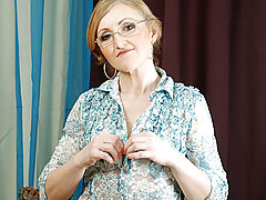Sweet grandmother with glasses slowly unbuttons her blouse