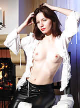 Brunette dominatrix Tinka seductively removes clothes in the chair